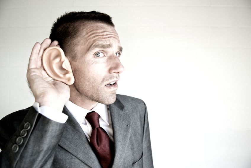 Project Manager holding oversized ear straining to hear